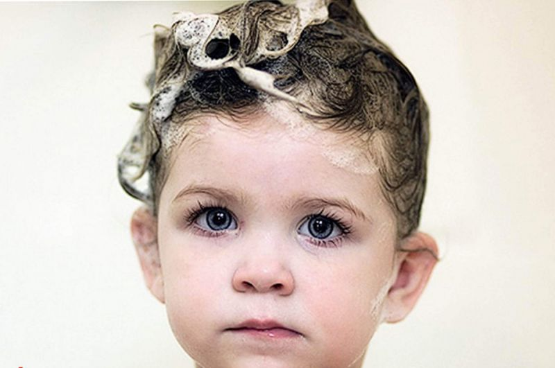 Child with soap suds on hair