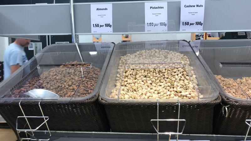 Three trays of self-service 'plastic-free' nuts in supermarket