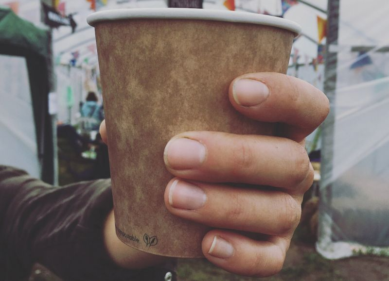 Hand holding Vegware compostable cup