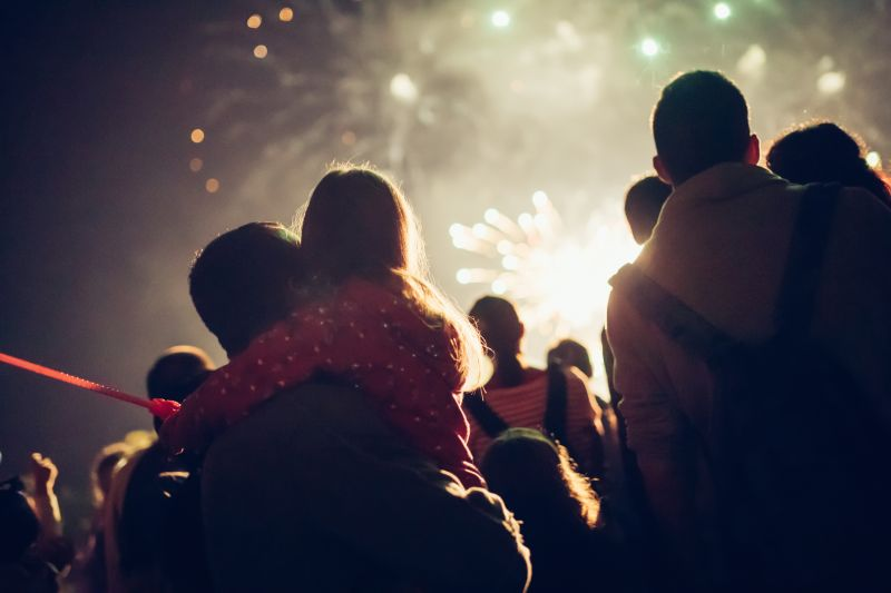 A father holds a young girl in his arms outdoors while standing in a crowd watching a firework display.