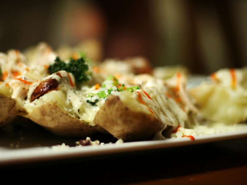 Plate of baked potatoes filled with vegetables and cheese