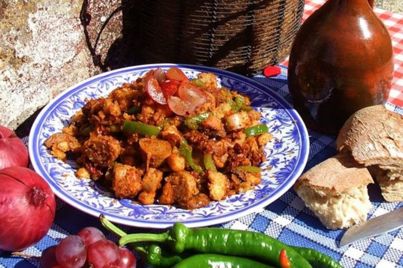Migas - bowl of traditional Spanish recipe bread salad on table. Onions, chili peppers and grapes around the dish.