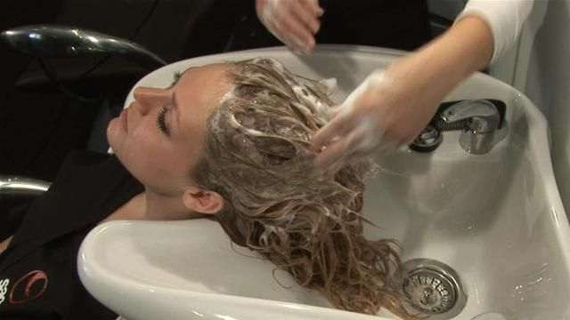 Girl having her hair shampooed at hairdressers sink