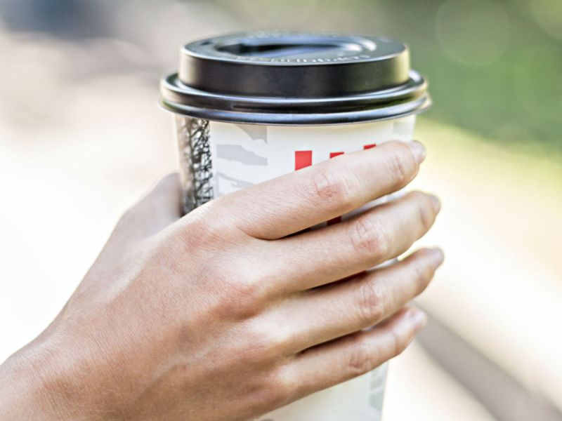 A close up of a woman's hand holding a takeaway coffee cup