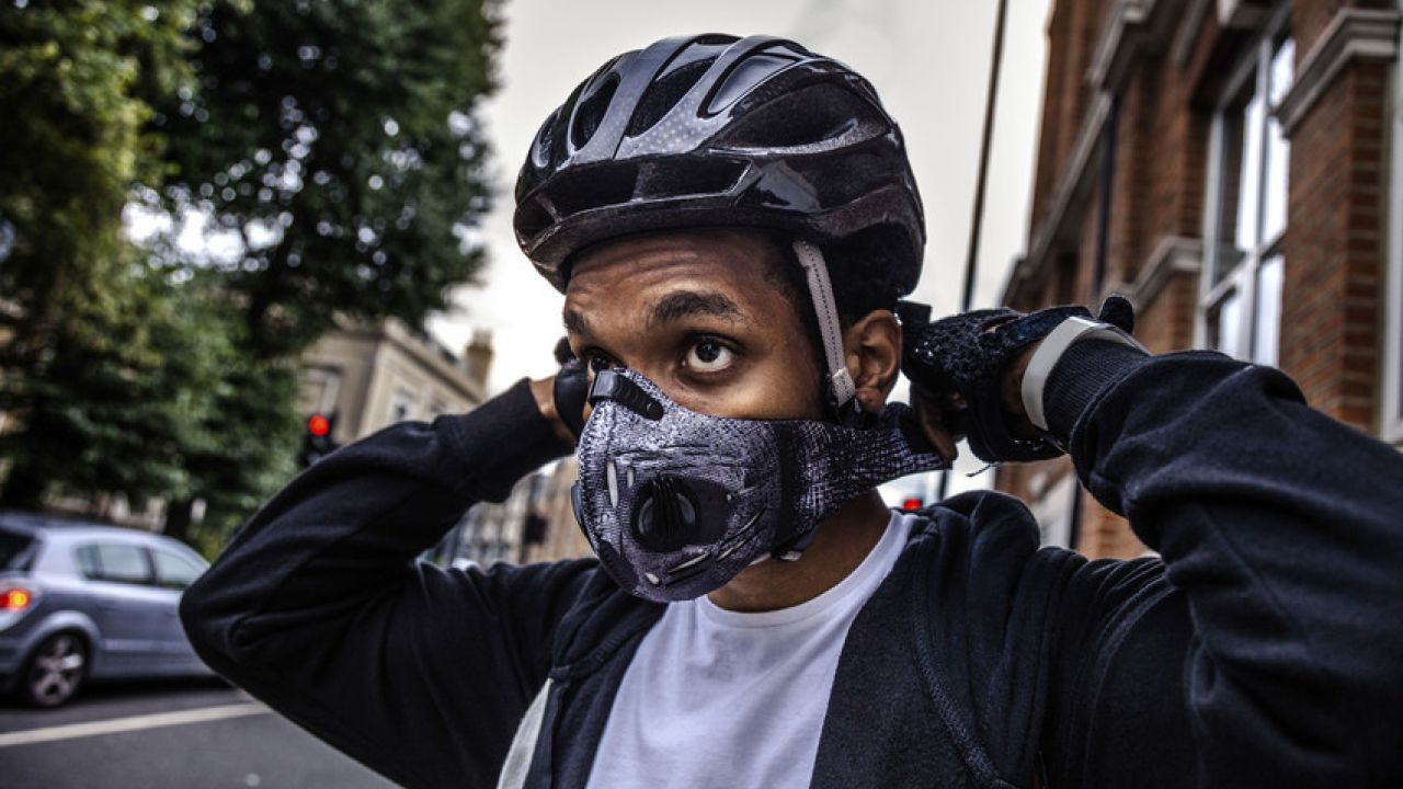 Male cyclist wearing helmet in street putting on anti-pollution mask .