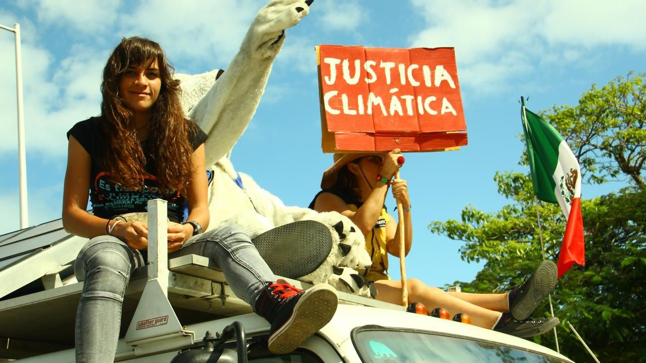 Two young women sitting on top of a van holding a placard which reads justicia climática