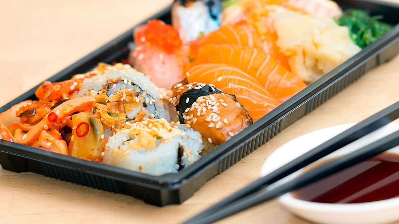 A black plastic food tray containing a sushi ready meal, with chopsticks