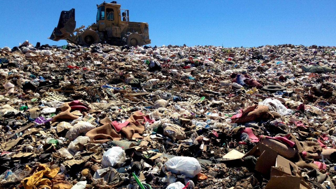 A digger moves through a pile of rubbish at a landfill site