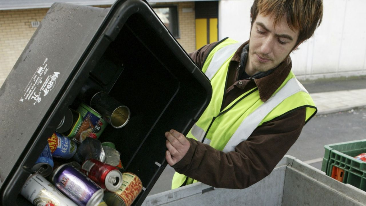 Man in hi-vis emptying a box of household recycling into a recycling van