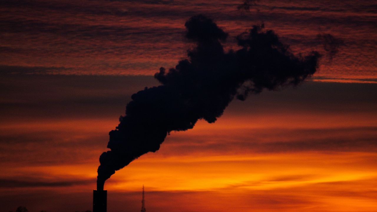 A photo taken at dusk showing a silhouette of the top of a factory emitting a lot of thick smoke