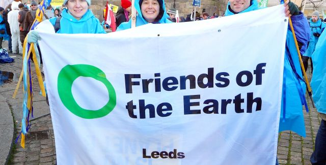 Group of people holding a Leeds Friends of the Earth local group flag