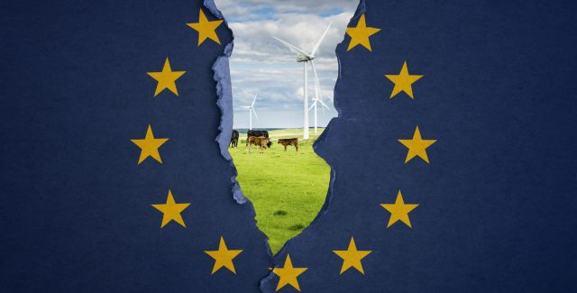 The EU flag ripping down the middle to reveal a field with wind turbines and cows
