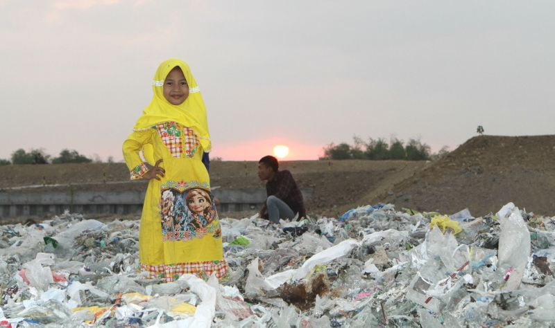 Child on a plastic waste dump, Surabaya, Indonesia