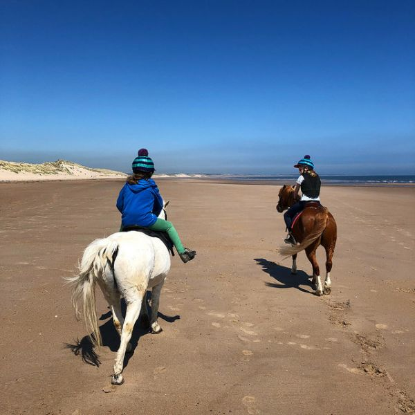 Children riding on Druridge Bay beach