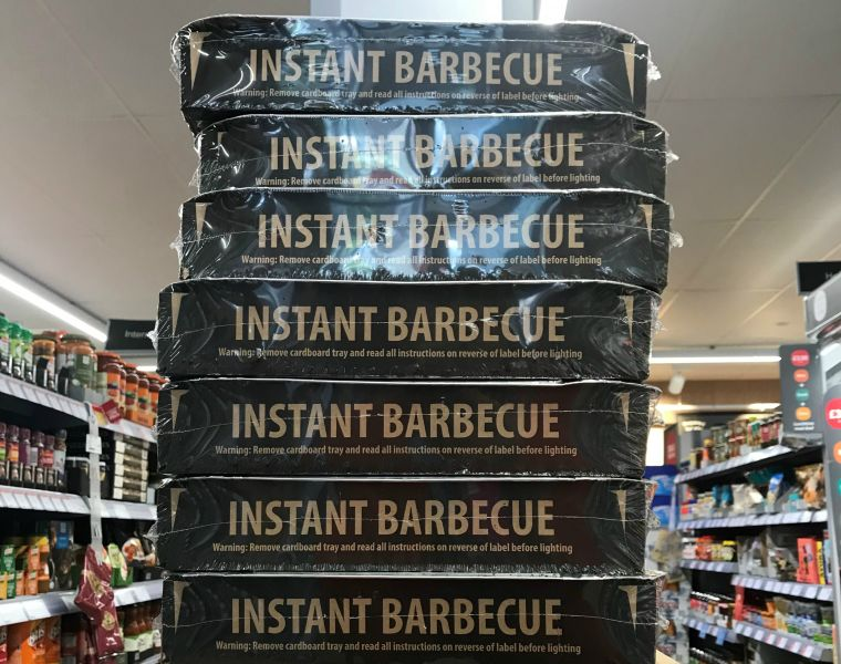 7 single-use plastic-wrapped barbecue trays stacked in supermarket