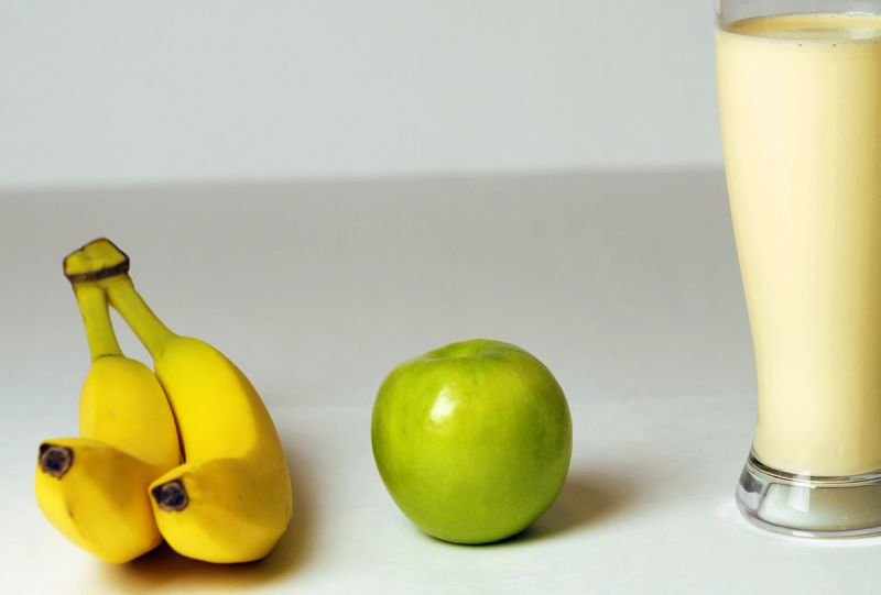 Yellow bananas, green apple and glass of milky smoothie
