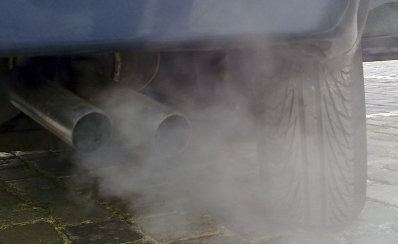 Car exhaust pipe emitting cloud of fumes