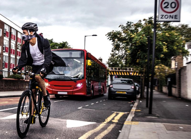 Cycling commuter wearing breathing mask, on busy road with buses and cars