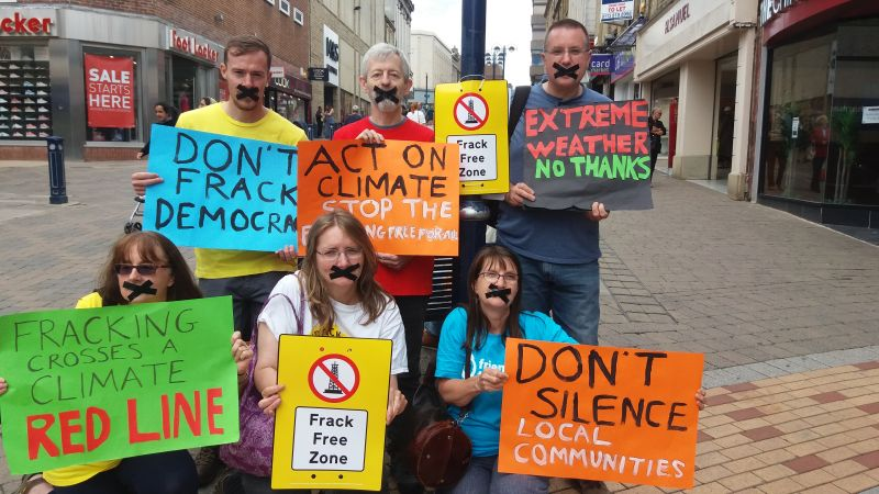 6 Huddersfield Friends of the Earth members in the street with placards protest against permitted developments.