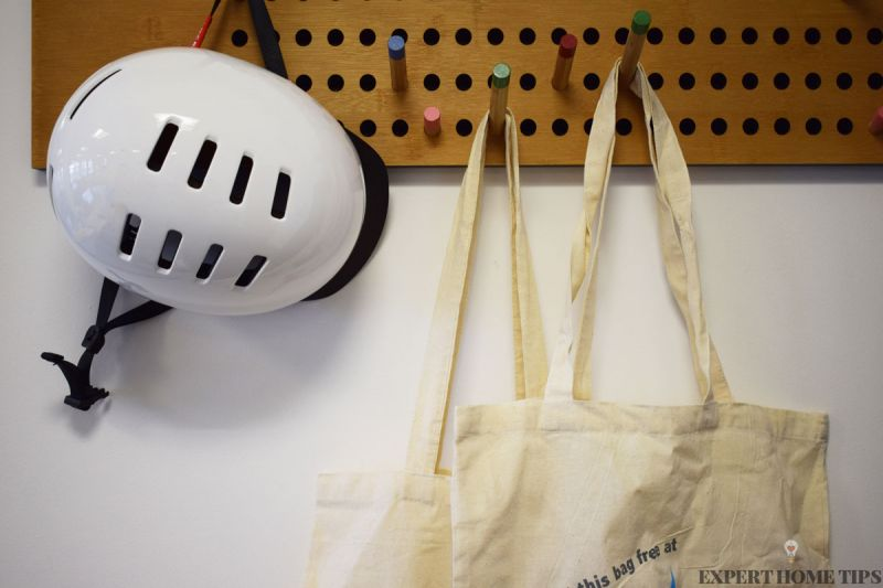 Canvas bags hanging on wooden peg board next to cycle helmet