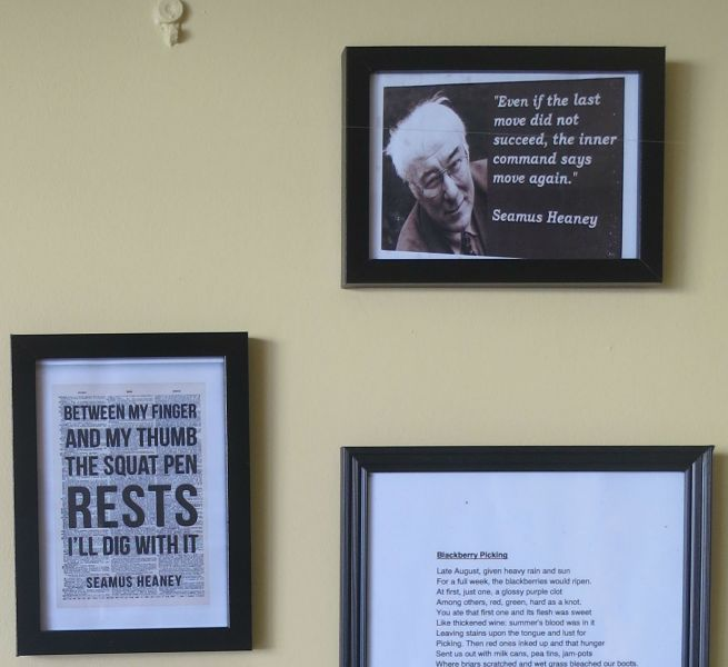 Framed photo of Seamus Heaney with quotation on wall. Plus a framed quotation and a framed poem.