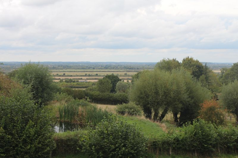 View of Otmoor from the village of Beckley: green trees and shrubs are dotted across a countryside landscape