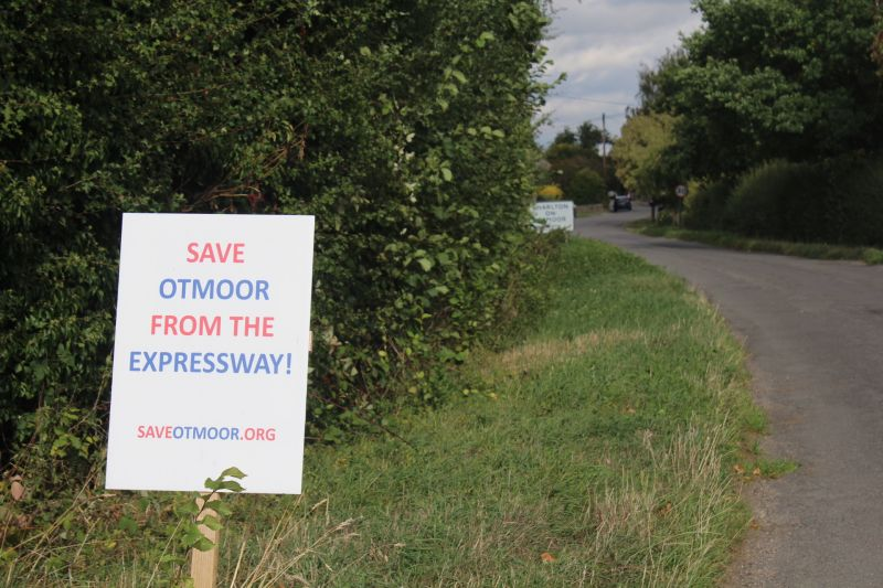 Save Otmoor sign on grass verge along country lane