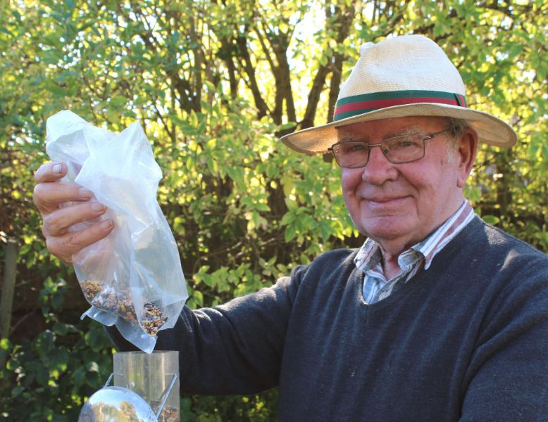 Ray Cobbett filling birdfeeders in his garden in Emsworth
