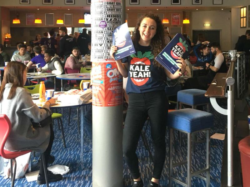 Katie holding Kale Yeah! posters and wearing a promotional t-shirt in the student bar at the University of Portsmouth