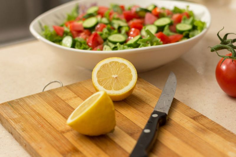 Lemon with salad and chopping board