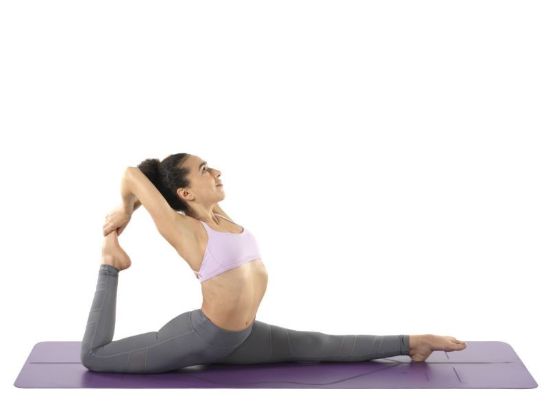 A woman practising yoga on a purple Liforme mat