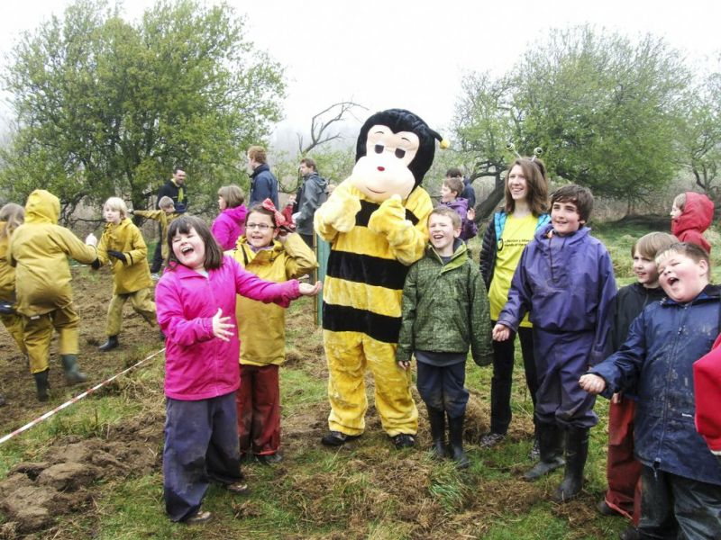 Person in bee costume and lots of children in field with trees in background