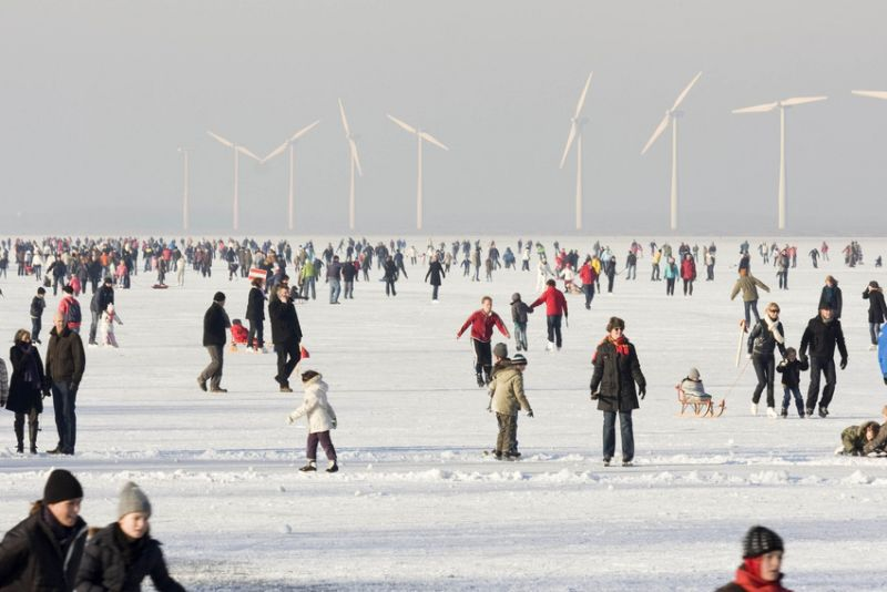 Photo of people ice skating with wind turbines in background