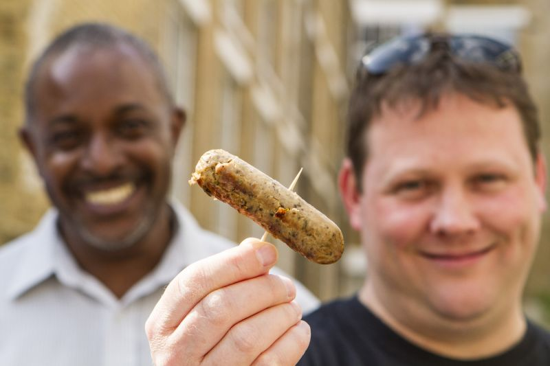 Two smiling protein-loving men hold a vegetarian sausage