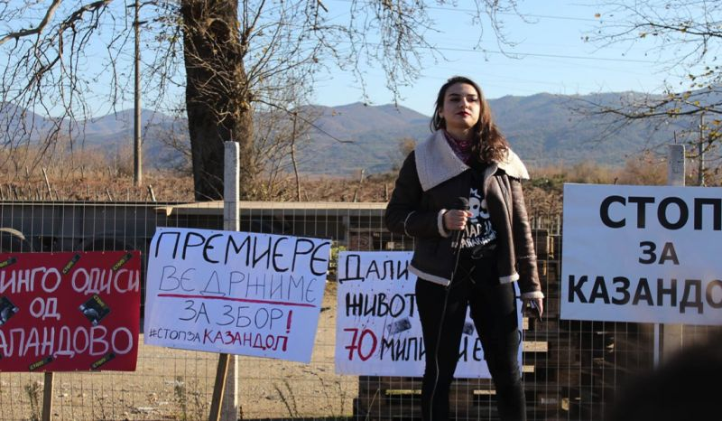 Young Macedonian activist Simona Getova, speaking in front of campaign banners