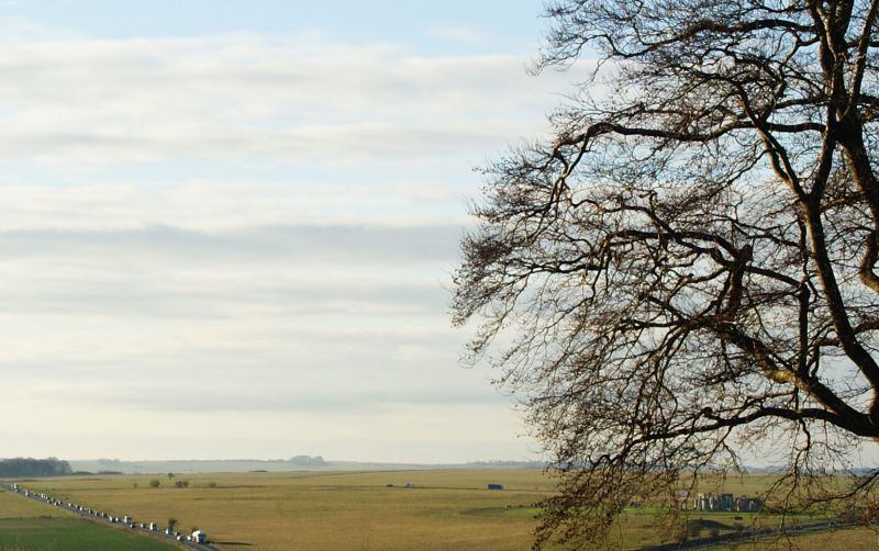 Panoramic view of flat Wiltshire countryside with busy A303 road and Stonehenge visible through trees