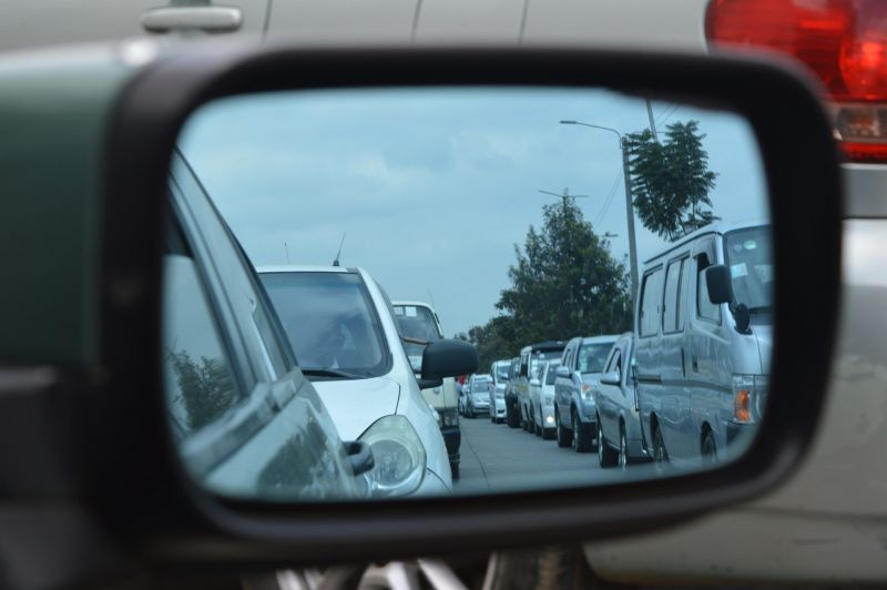 Long traffic jam viewed in car wing mirror