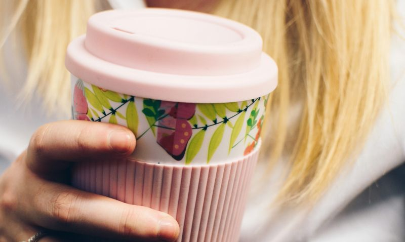 Woman holding a pink reusable takeaway cup