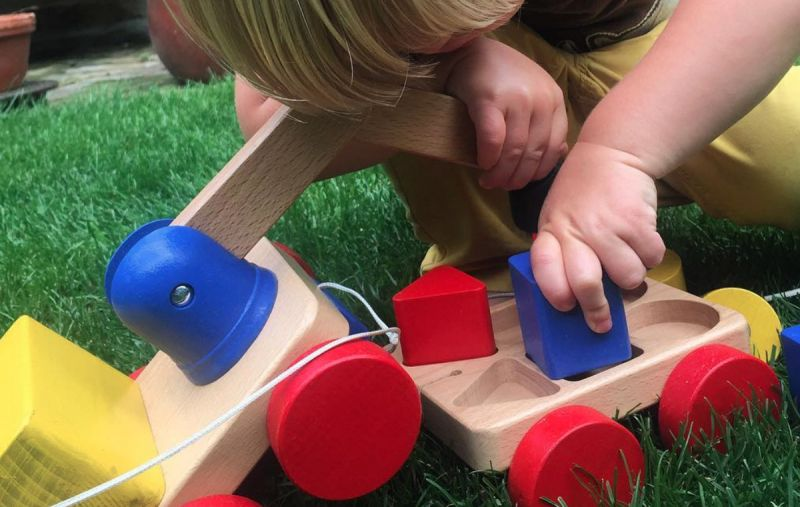 Toddler playing with colourful wooden toy crane on wheels