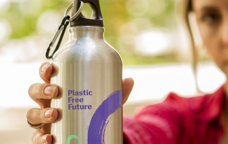 Close-up of woman holding Friends of the Earth Plastic-Free aluminium water bottle