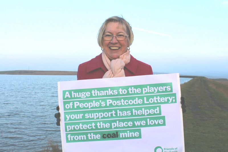 Alyson Austin of Merthyr Tydfil Friends of the Earth smiles for the camera as she stands by a lake holding a placard thanking the People's Postcode Lottery for funding.