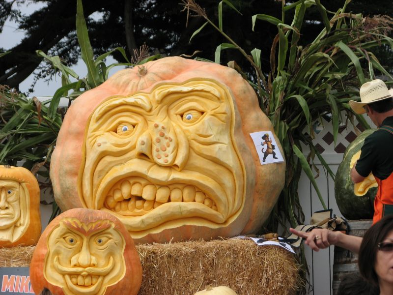 3 pumpkins with artistic carved faces on show at the Half Moon Bay Pumpkin Festival 2011