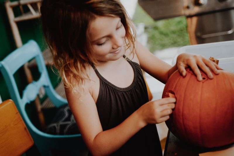 Artificial pumpkins are a poor substitute for the real thing. Young girl carving pumpkin