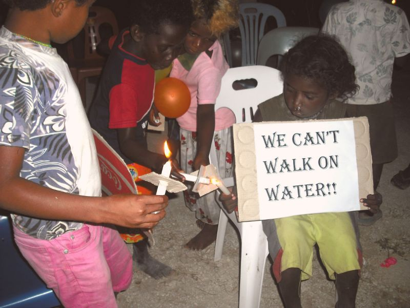 "Children lighting candles in Papa New Guinea. One holds a sign saying ""We can't walk on water!!"""