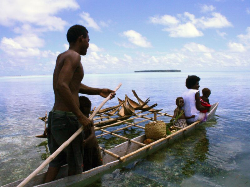 A man rows his family to an unknown destination on a long narrow boat in the waters of Papa New Guinea