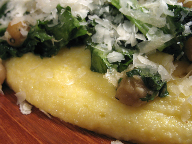 Vegetarian dish of chickpeas and greens on a bed of polenta