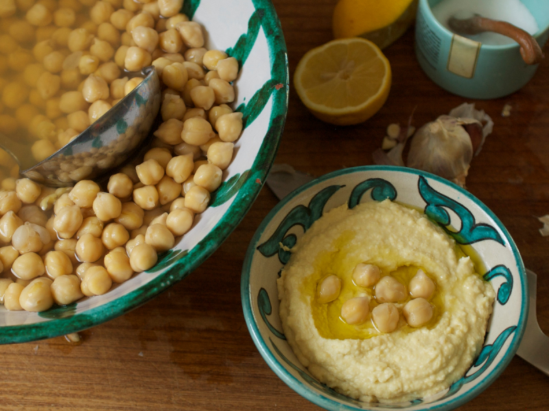 Chickpeas in a bowl alongside a small dish of homemade hummus