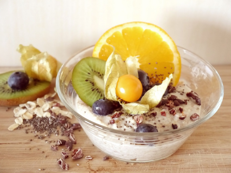 Oat porridge in a bowl with a fresh fruit topping including orange and kiwi