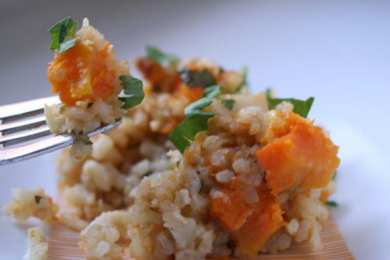 A small portion of vegetarian butternut squash risotto with a forkful of risotto above it.
