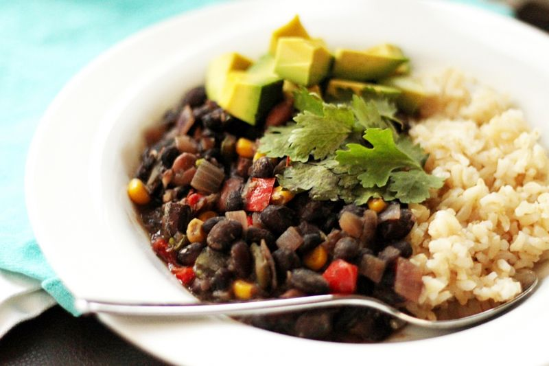 Vegetarian chilli in a bowl with black beans and quorn, served with rice and avocado